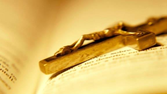Ein Kruzifix auf einer aufgeschlagenen Bibel