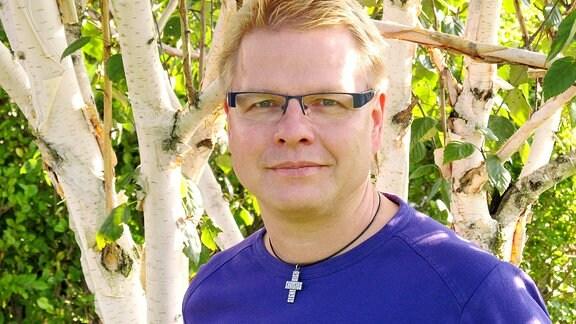 Ein Mann steht vor einem Baum und schaut lächelnd in die Kamera. Pfarrer Christof Lenzen aus der Freien evangelischen Gemeinde Gera.
