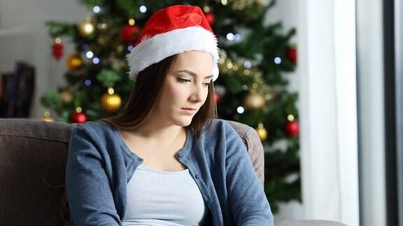 Eine Frau mit Weihnachtsmütze, sitzt alleine auf der Couch.