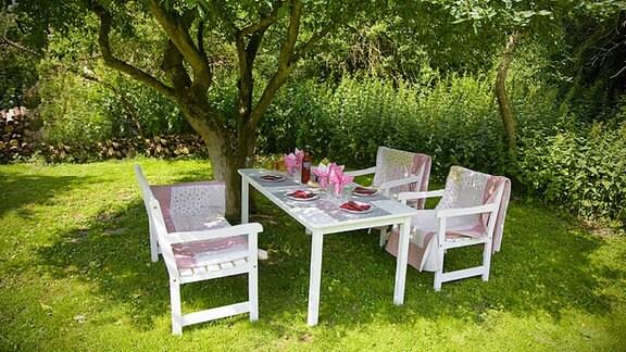 Vier Stühle und ein gedeckter Tisch stehen unter einem Baum auf einer Wiese