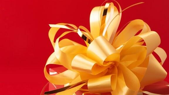 Eine gelbe Schleife auf einem roten Geschenk