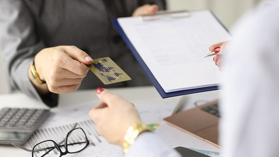 Eine Kreditkarte wird über den Tisch gereicht.