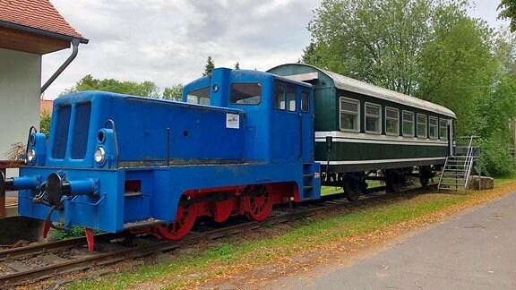 Eine blaue Lok, dahinter ein grüner Eisenbahnwaggon