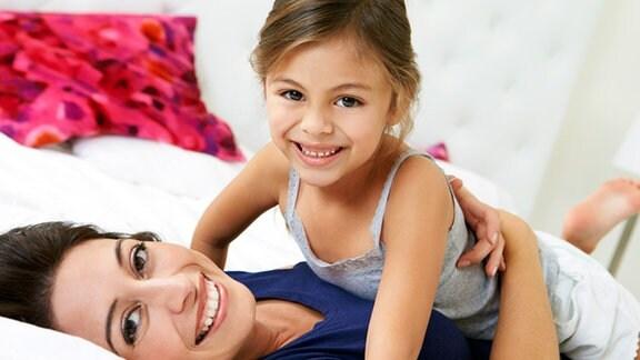 Eine Mutter kuschelt mit ihrer kleinen Tochter.