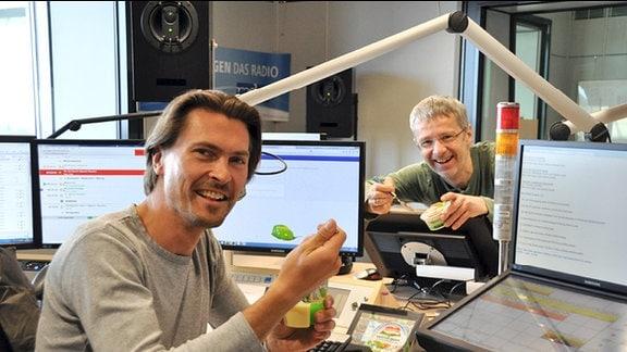 MDR-Moderator Johannes-Michael Noack sitzt in einem Hörfunk-Studio an einem Pult und isst einen Löffel grüne Grütze. Sein Kollege Matthias Haase steht hinter dem Pult und hält eine Grütze-Packung in der Hand.