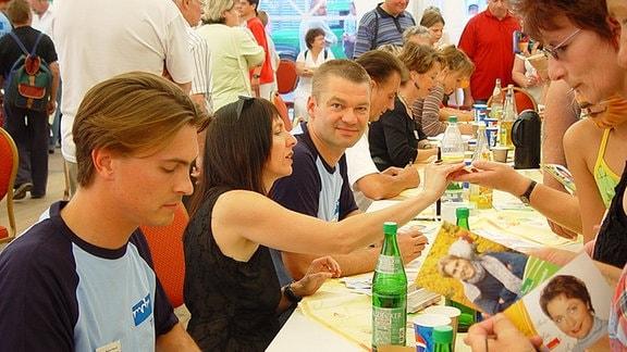 Die MDR 1 Radio Thüringen-Moderatoren Johannes-Michael Noack, Christiane Weber und Frank Huber sitzen an einem Tisch und geben Autogramme.