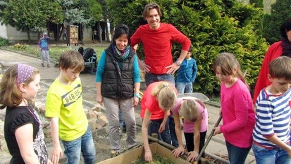 Kinder und Erwachsene arbeiten in einem Garten