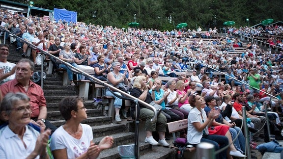 Zuschauer bei einem von MDR THÜRINGEN präsentierten Solo-Konzert mit Chris de Burgh im Naturtheater Steinbach-Langenbach spenden Applaus