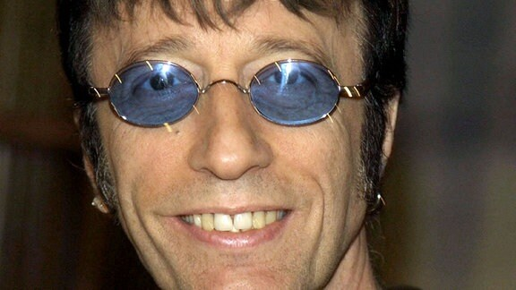 Ein Mann mit blauer, ovaler Sonnenbrille schaut lächelnd in die Kamera.