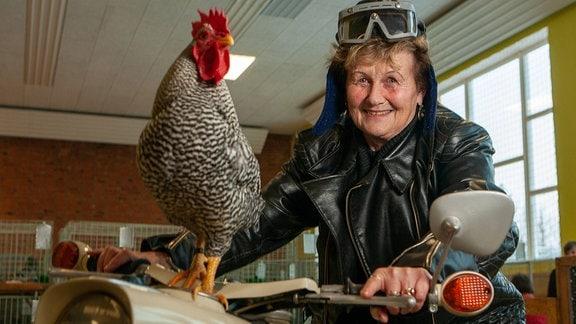 Thea Minkwitz auf einem Motorrad sitzend und einem Hahn der Rasse Zwerg Amrocks