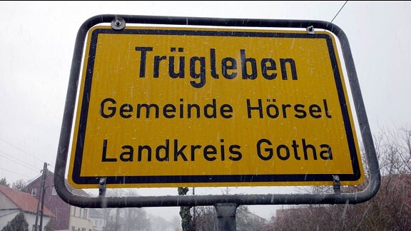 """Ein Ortseingangsschild mit der Aufschrift """"Trügleben Gemeinde Hörsel Landkreis Gotha"""" bei Schneeregen"""