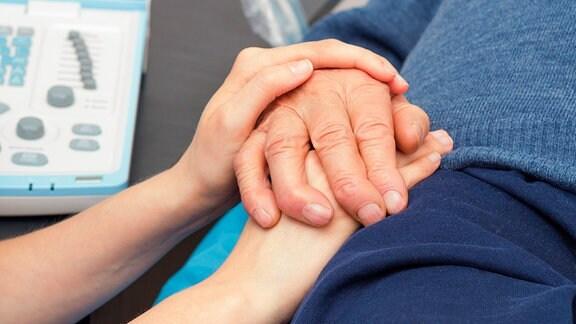 Krankenschwester hält Hand eines Patienten