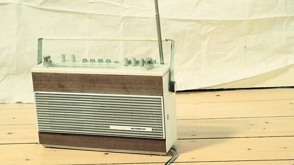 Ein älteres Radiogerät steht auf einem Holzfußboden.