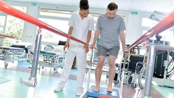 Ein Patient übt das Gehen unter Anleitung einer Therapeutin an einer Stange.
