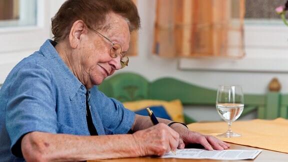 Eine alte Frau schreibt auf einem Blatt