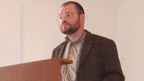 Mann mit Bart und Brille an Pult
