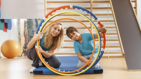 zwei junge Menschen schauen durch hula-hoop-Reifen