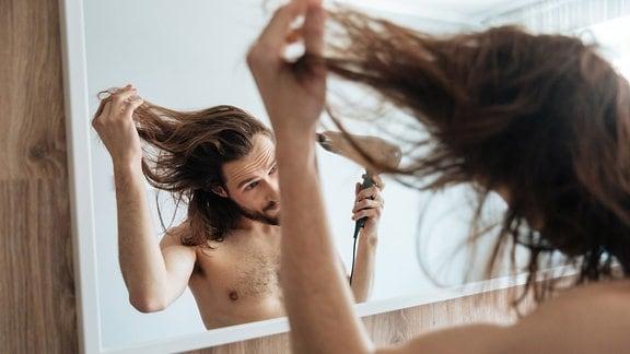 Mann föhnt lange Haare