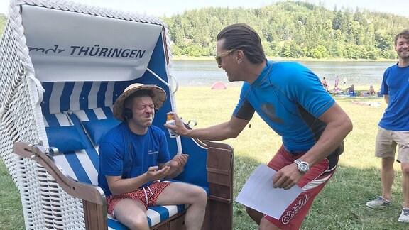 Johannes sprüht Marko mit Sonnenschutz ein.