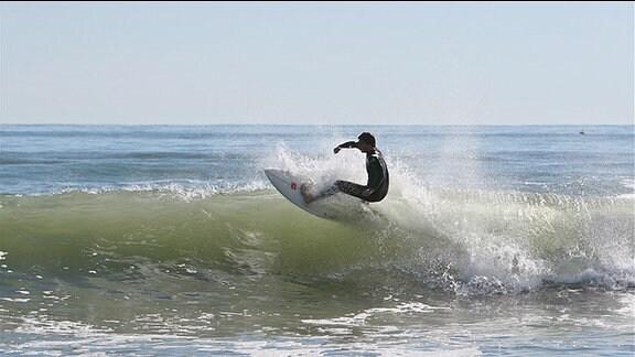 Ein Surfer auf seinem Board