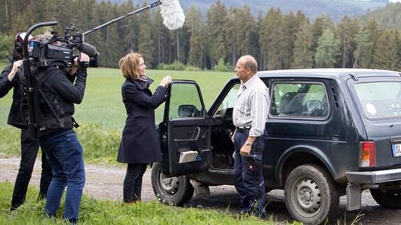 Mann steht an geöffnetet Pkw Tür und wird von einem Kamerateam gefilmt und interviewt.