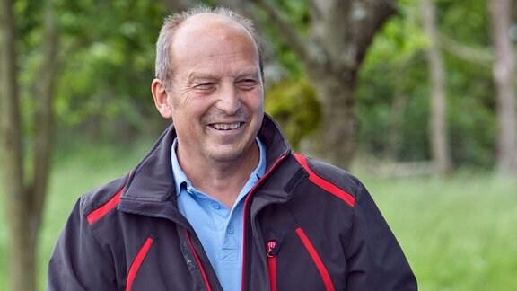 Mann mit Urkunde schaut lächelnd in die Kamera.