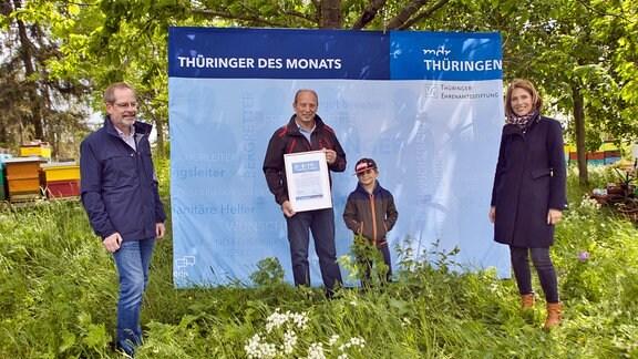 Thüringer des Monats Mai vor Aufsteller mit Urkunde in den Händen.