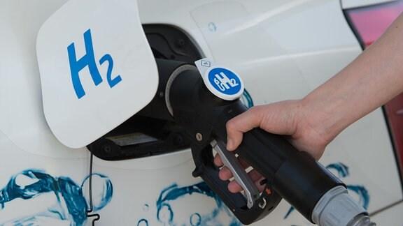 Ein Zapf-Ventil von einer Wasserstoff-Tankstelle steckt im Tankstutzen eines Wasserstoffautos.