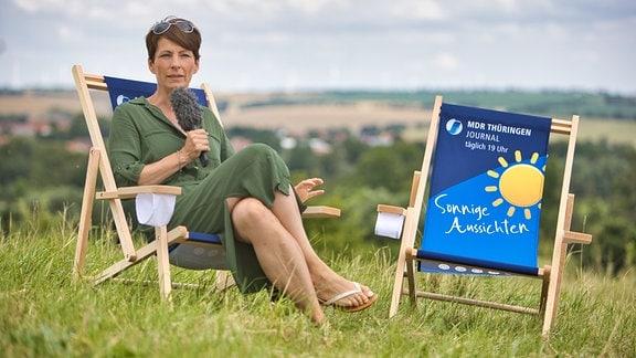 """Die Moderatorin Sandra Voigtmann sitzt auf einem Liegestuhl mit der Aufschrift """"Sonnige Aussichten"""" in einer Wiese"""