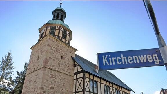 """Ansicht einer Kirche in Wichtshausen (Suhl). Im Vordergrund ist das Straßenschild """"Kirchenweg"""" zu lesen."""