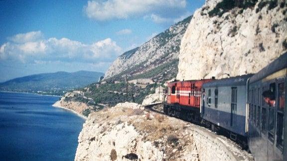 Ein Zug fährt an einer Steilküste entlang.
