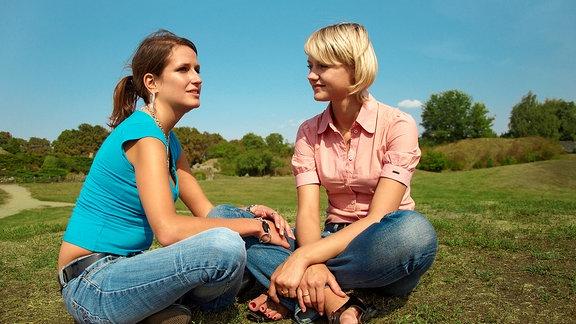 Zwei junge Frauen sitzen auf einer Wiese