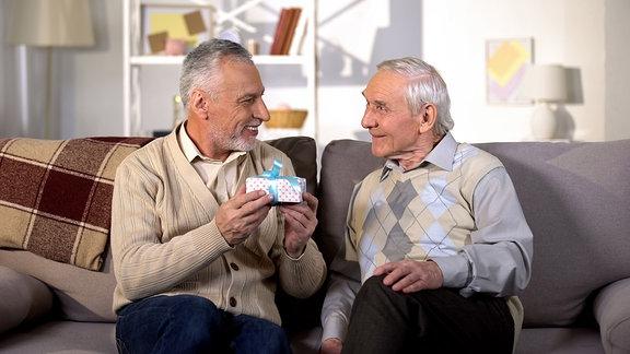 Zwei ältere Männer sitzen auf einem Sofa, einer hält ein kleines Geschenk
