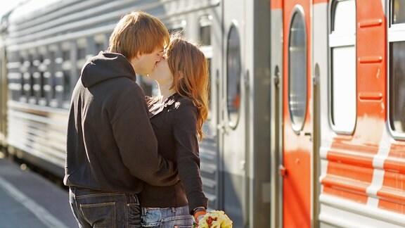Ein junger Mann küsst eine junge Frau auf einem Bahnsteig