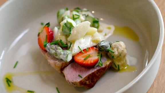 Teller mit Fleisch, Erdbeere und Salat