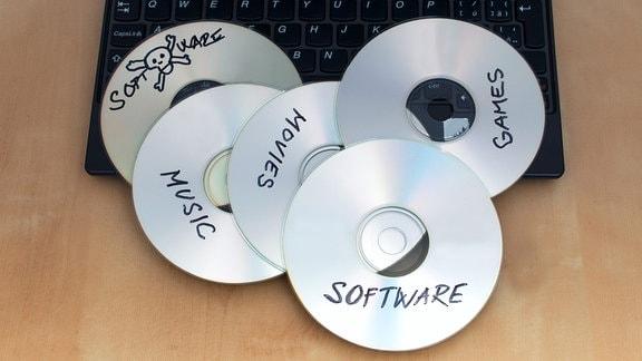 Ein Laptop mit mehreren gebrannten CDs