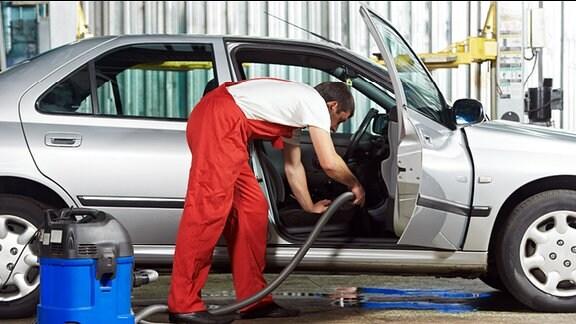 Ein Mann saugt im Innenraum eines Autos.