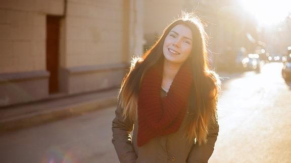 Junge Frau posiert im Parka mit Schal