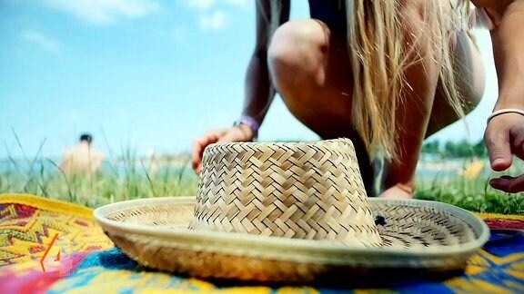 EIne Frau bückt sich nach einem Sonnenhut am Strand.