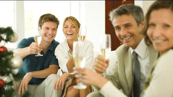 Männer und Frauen stoßen mit Sektgläsern an