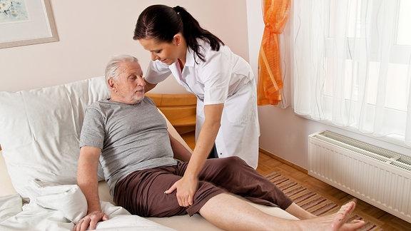 Eine Pflegerin betreut einen älteren Mann