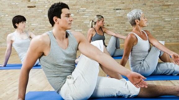 Eine Gruppe von Menschen betreibt Gymnastik am Boden