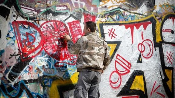 Ein Junge sprüht ein Graffiti an eine Wand.