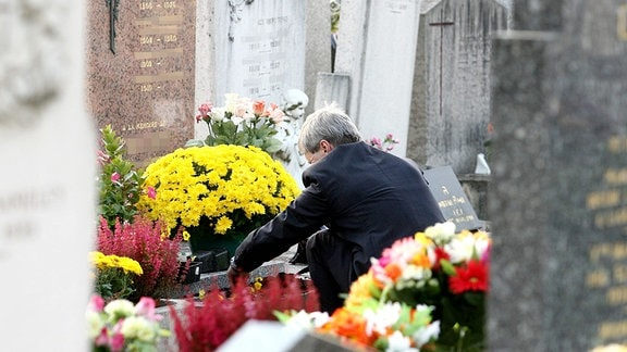 Auf einem Friedhof, ein Mann hockt vor einem Grab und bringt Blumen.