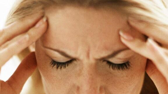 Eine Frau fasst sich mit beiden Händen an die Stirn
