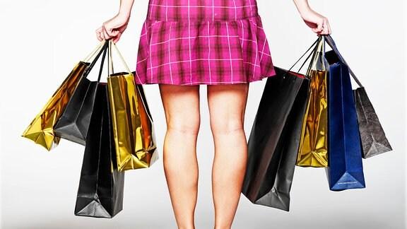 Frau, mit vielen bunten Einkaufstüten bepackt