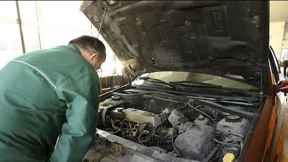 Ein Mechaniker steht vor einer offenen Motorhaube eines Autos.