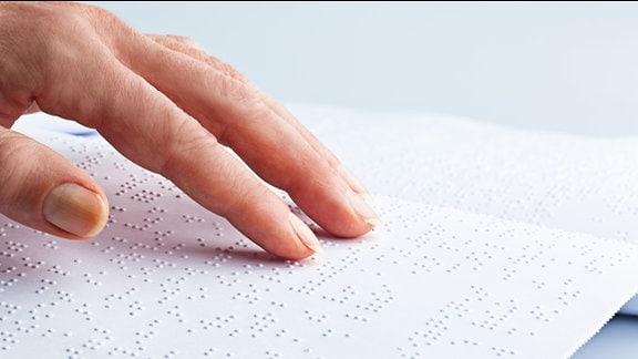 Finger fahren über eine Seite mit Brailleschrift