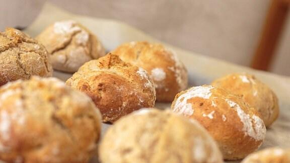 Frisch gebackene Brötchen liegen auf einem Ofenbackblech.