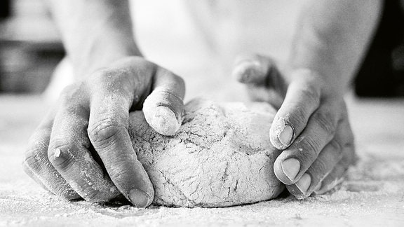 zeigt Hände, die einen Brotteig kneten